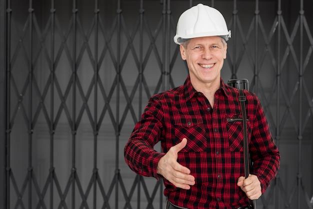 Smiley ingeniero masculino listo para estrecharle la mano