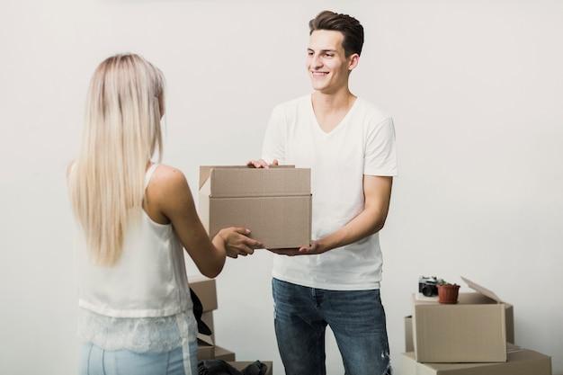 Smiley joven hombre y mujer con caja