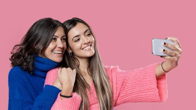 Smiley mamá e hija tomando selfie