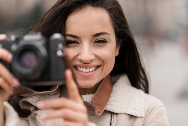 Smiley mujer fotógrafa tomando una foto