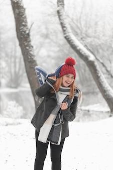 Smiley mujer y trineo paisaje invernal