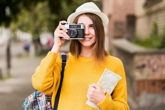 Smiley mujer viajando tomando una foto