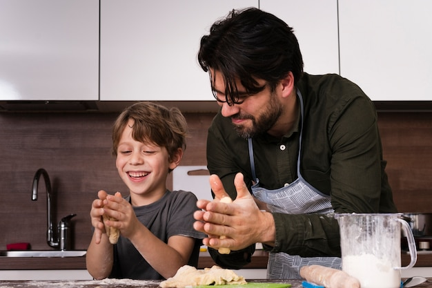 Smiley padre e hijo rodando masa