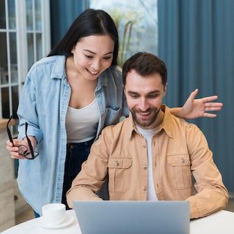 Smiley pareja de compras en línea en la computadora portátil