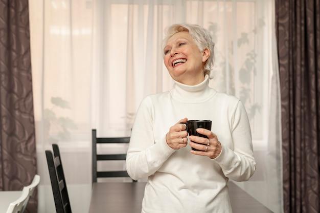 Smiley senior femenino sosteniendo la taza de café