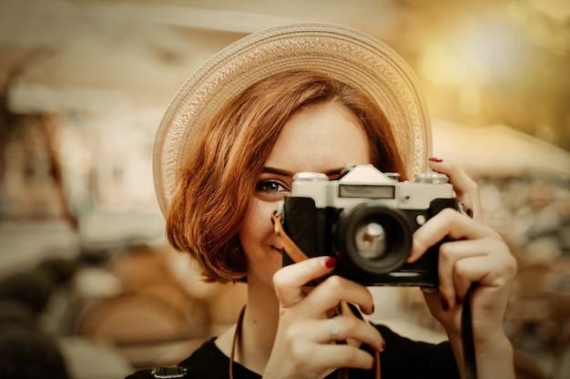 Smilling hipster mujer sosteniendo una cámara retro en sus manos y tomando una foto