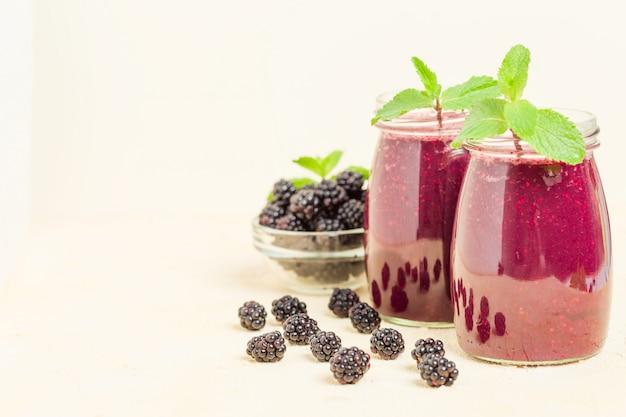 Smoothie de blackberry - bebida cruda orgánica con las bayas maduras frescas del bosque en fondo amarillo en colores pastel.