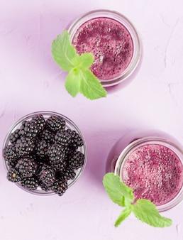 Smoothie de blackberry - bebida orgánica cruda con las bayas maduras frescas del bosque en fondo violeta en colores pastel.