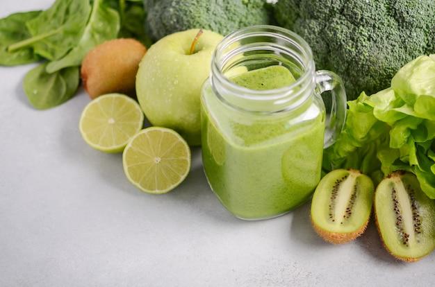 Smoothie verde fresco en un tarro con los ingredientes en un fondo concreto gris, foco selectivo.