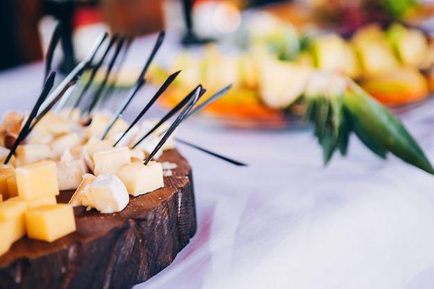 Smorgasbord. desayuno buffet. servicios de banquetería. pequeños sándwiches, queso y uvas en una brocheta, tartas pequeñas, tomates cherry con verduras, aceitunas con carne, un plato de queso.