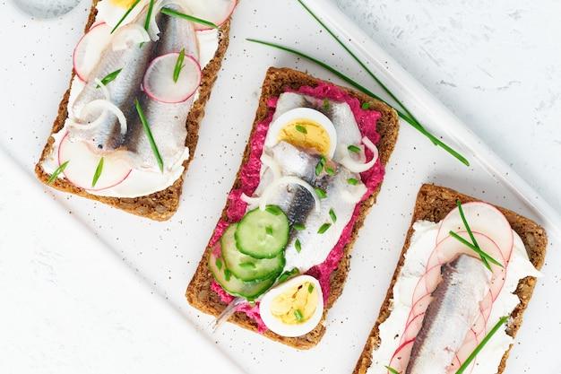Smorrebrod salado, conjunto de bocadillos daneses tradicionales. pan de centeno negro con anchoa, remolacha, rábano, huevos, queso crema en plato gris sobre mesa de piedra blanca