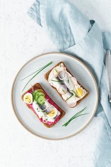 Smorrebrod salado, dos sándwiches tradicionales daneses. pan de centeno negro con anchoa, remolacha
