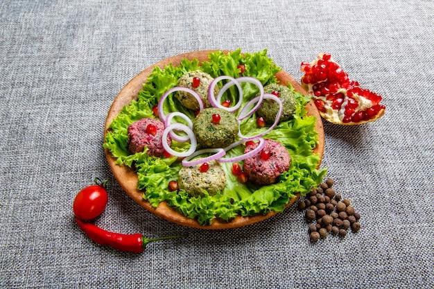 Snack phali en forma de bolitas de colores a base de verduras: espinacas, coliflor y remolacha. el plato es parecido a un paté con salsa de ajo, hierbas, nueces y lúpulo suneli. sobre un lienzo gris