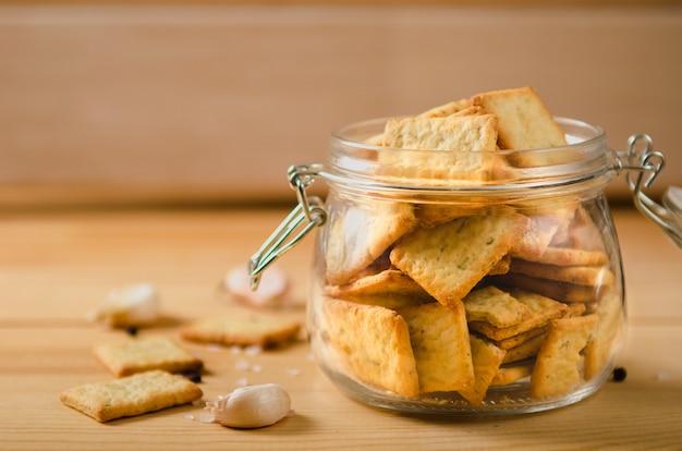 Snacks salados con pimienta, sal, verduras en un frasco de vidrio en una mesa de madera