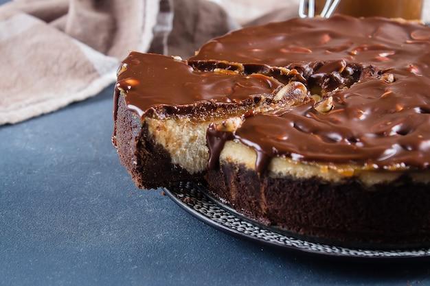 Snickers de tarta de queso con caramelo, turrón y pastel de cacahuate sobre fondo de hormigón azul
