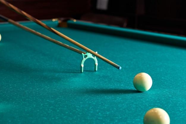 Snooker - primer plano de hombre jugando al billar, mesa azul con bolas blancas en él