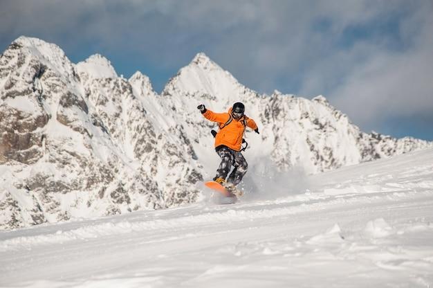 Snowboarder activo montando en la ladera de la montaña