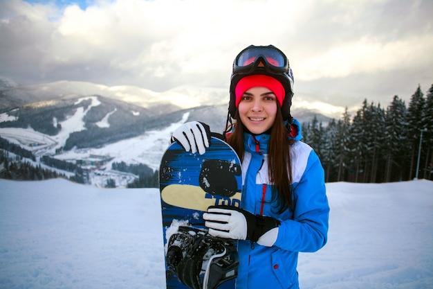 Snowboarder alegre mujer en invierno en la estación de esquí