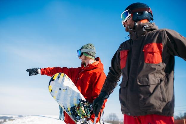 Snowboarder y esquiador posa en la cima de la montaña, cielo azul. deporte activo de invierno, estilo de vida extremo, snowboard y esquí