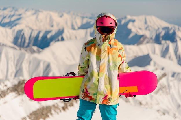 Snowboarder femenino en ropa deportiva de pie en la cima de la montaña nevada