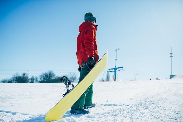 Snowboarder en gafas posa con tablero en manos
