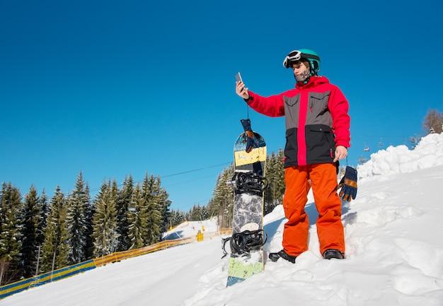 Snowboarder macho descansando en la ladera en la estación de esquí, usando su teléfono inteligente después de snowboard