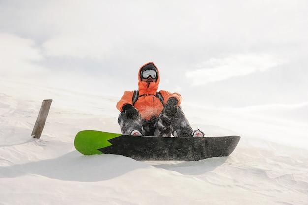 Snowboarder masculino cabalgando por la colina de montaña en el tablero. snowboard en georgia, goderdzi