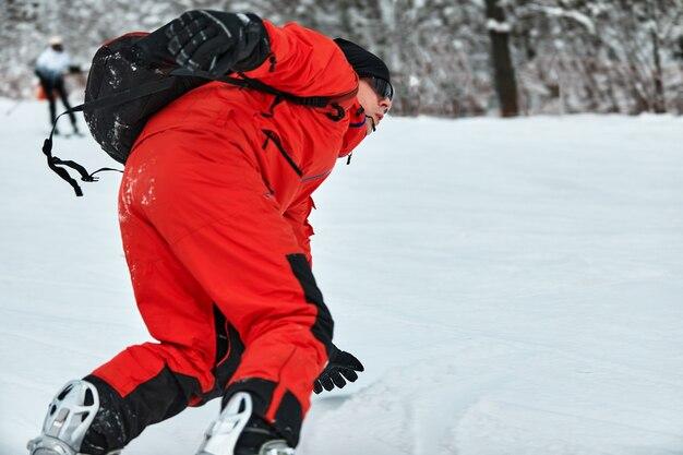 Snowboarder masculino en un traje rojo cabalga sobre la colina nevada con concepto de snowboard, esquí y snowboard.