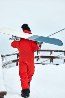 Snowboarder masculino en un traje rojo caminando sobre la colina nevada con concepto de snowboard, esquí y snowboard.