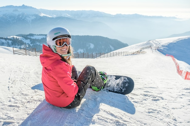 Snowboarder niña sentada con tabla en la pista de esquí en las montañas