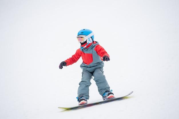 Snowboarder niño montando sobre la pendiente en las montañas