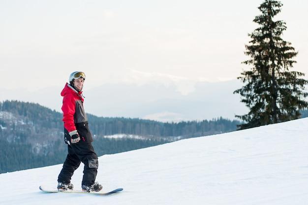 Snowboarder de pie en la cima de una montaña