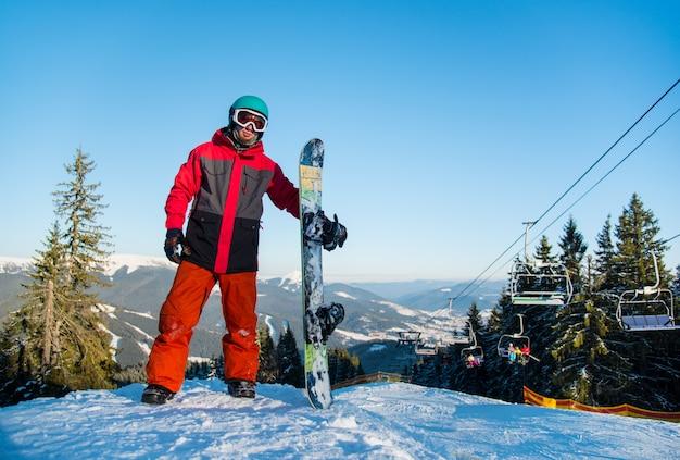 Snowboarder de pie con su tabla de snowboard en la cima de la montaña después de montar en la estación de esquí de invierno