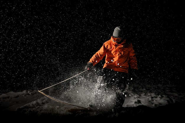 Snowboarder profesional masculino cabalgando sobre la nieve por la noche