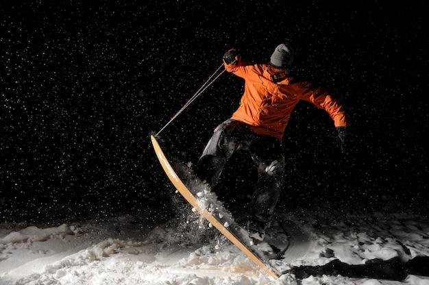 Snowboarder profesional masculino saltando sobre la nieve por la noche