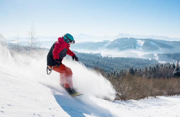 Snowboarder profesional montando en las montañas