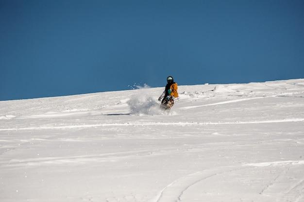 Snowboarder en ropa deportiva montando en la ladera de la montaña