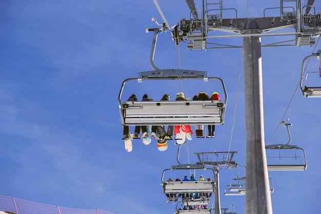 Snowboarders con equipo subiendo con telesilla