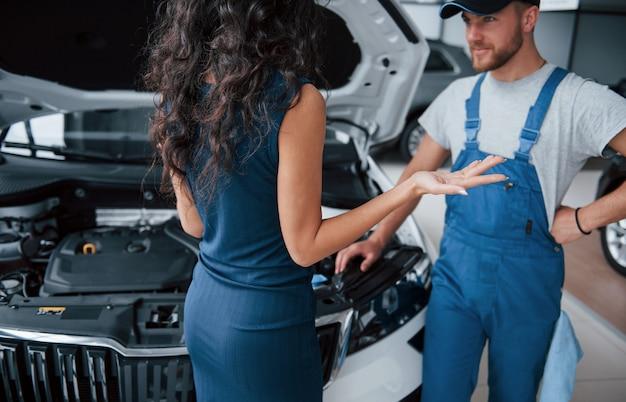 Sobre ese accidente. mujer en el salón del automóvil con empleado en uniforme azul tomando su auto reparado