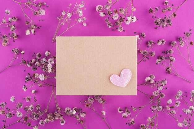 Sobre de artesanía en superficie rosa con flores