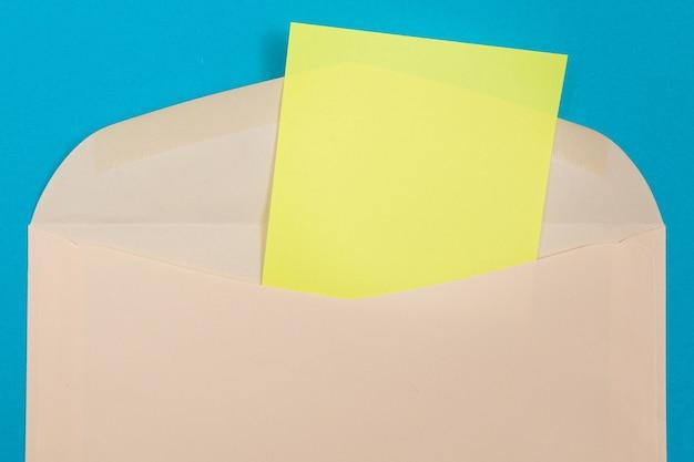 Sobre beige con hoja de papel amarillo en blanco dentro