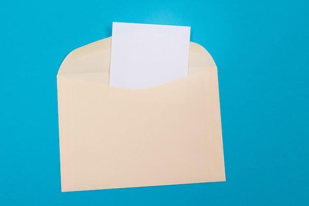 Sobre beige con hoja de papel en blanco en el interior