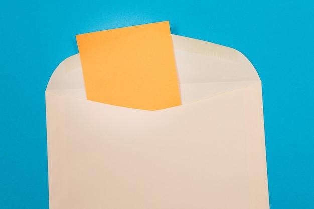 Sobre beige con hoja de papel naranja en blanco dentro