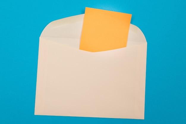 Sobre beige con hoja de papel naranja en blanco en el interior