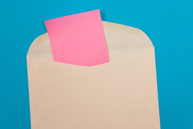 Sobre beige con hoja de papel rosa en blanco en el interior