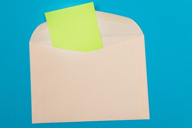 Sobre beige con hoja de papel verde en blanco dentro