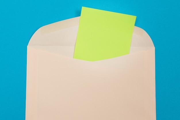 Sobre beige con hoja de papel verde en blanco en el interior acostado sobre fondo azul maqueta con copia sp ...