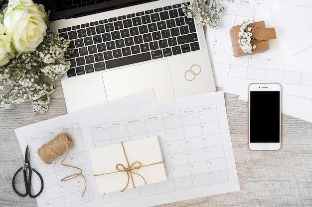 Sobre; calendario; ordenador portátil; flores; teléfono inteligente; carrete; cuaderno de tijera y espiral en mesa de madera.