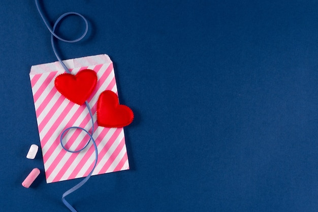 Sobre de carta de amor con corazones rojos y tiza sobre fondo de color azul clásico 2020 tendencia. día de san valentín 14 de febrero concepto de embalaje. lay flat, espacio de copia, vista superior, banner.