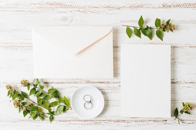 Sobre cerrado; tarjeta; ramita de flores y anillos de boda en un plato sobre el escritorio blanco